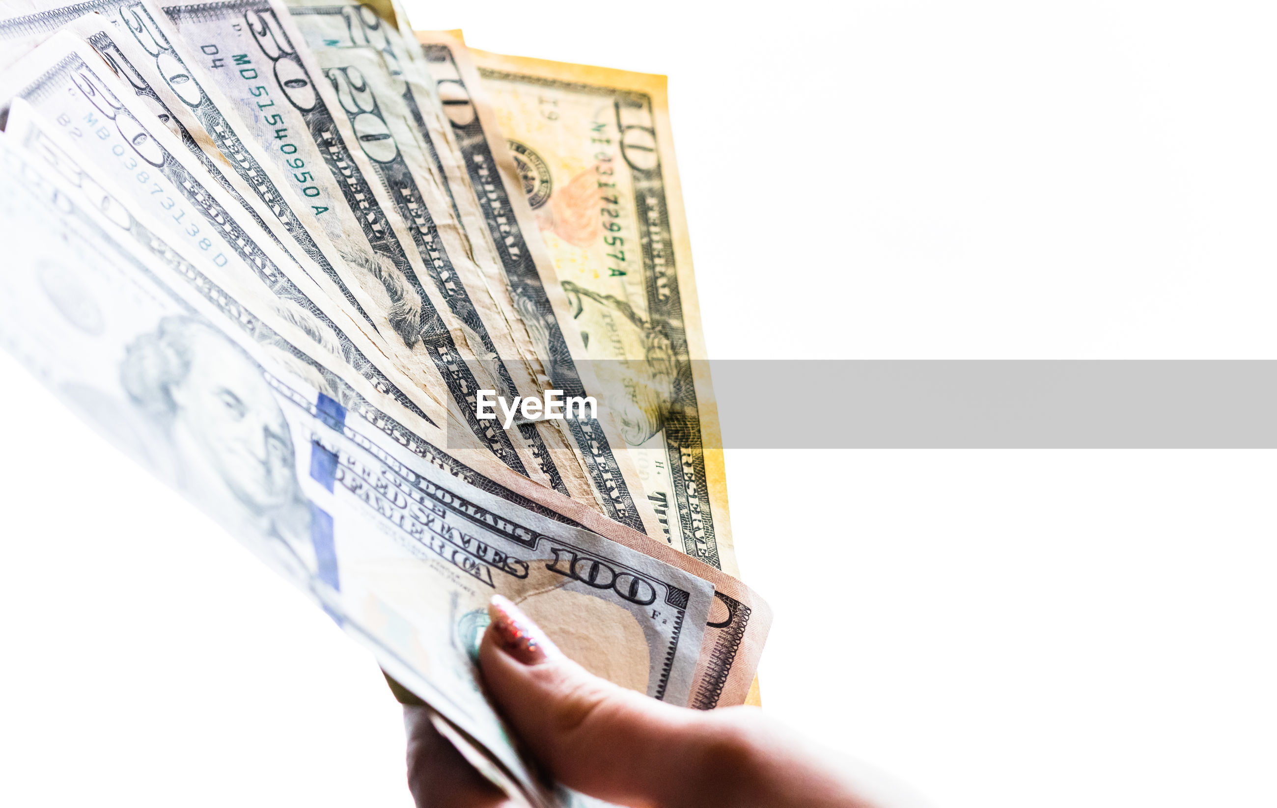 Close-up of hand holding paper currency against white background