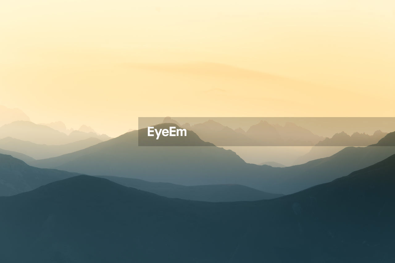 mountain, scenics - nature, sky, beauty in nature, tranquility, tranquil scene, mountain range, sunset, idyllic, non-urban scene, silhouette, environment, landscape, no people, nature, majestic, fog, copy space, remote, outdoors, mountain peak, hazy