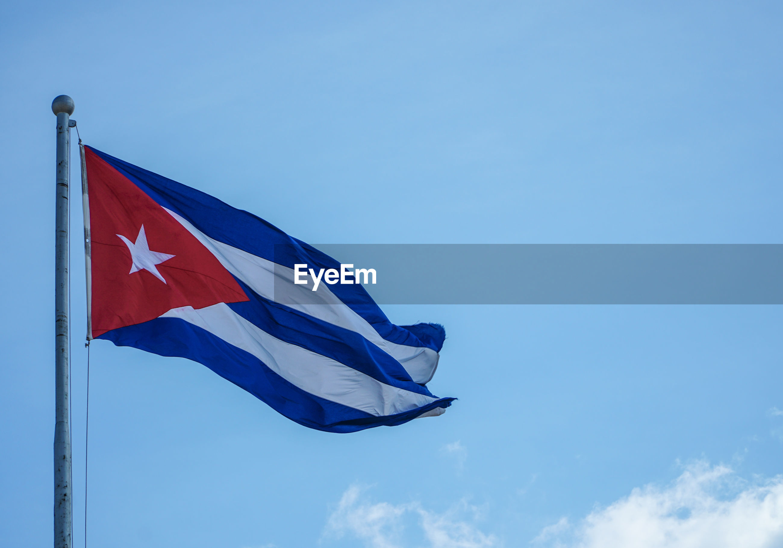 Low angle view of cuban flag against blue sky