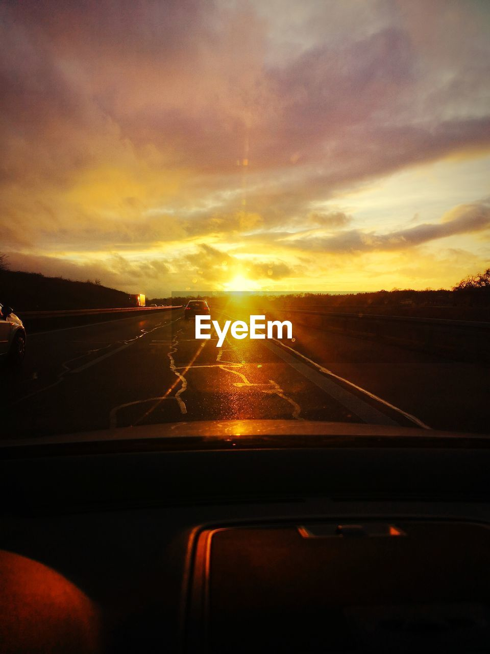 sunset, sky, car, vehicle interior, transportation, mode of transportation, glass - material, motor vehicle, sun, transparent, cloud - sky, nature, car interior, land vehicle, orange color, windshield, sunlight, road, lens flare, on the move, no people, outdoors, car point of view, road trip