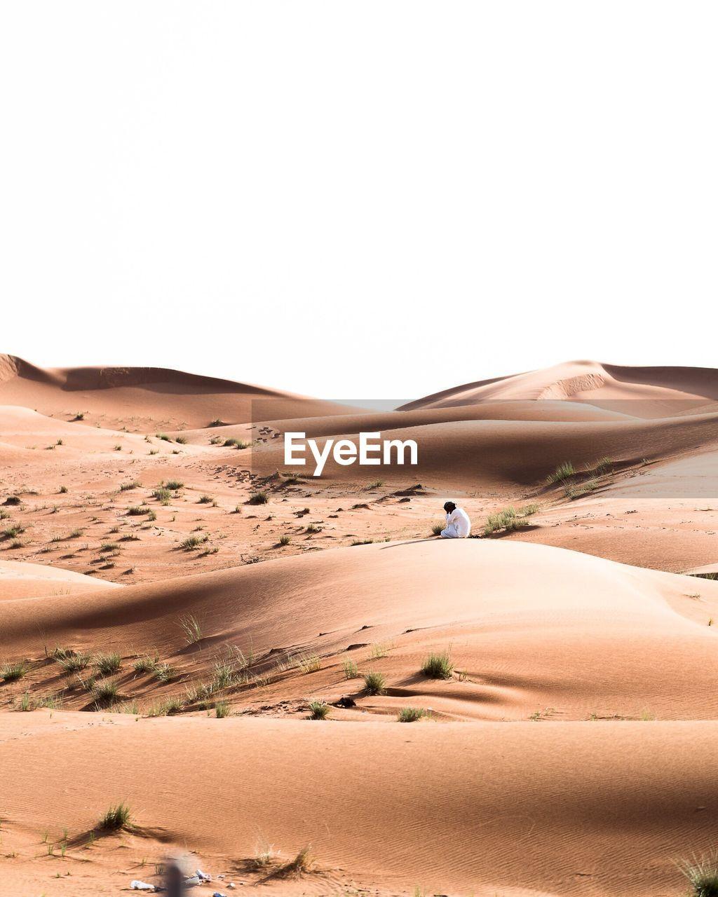 Man Sitting On Desert Against Clear Sky