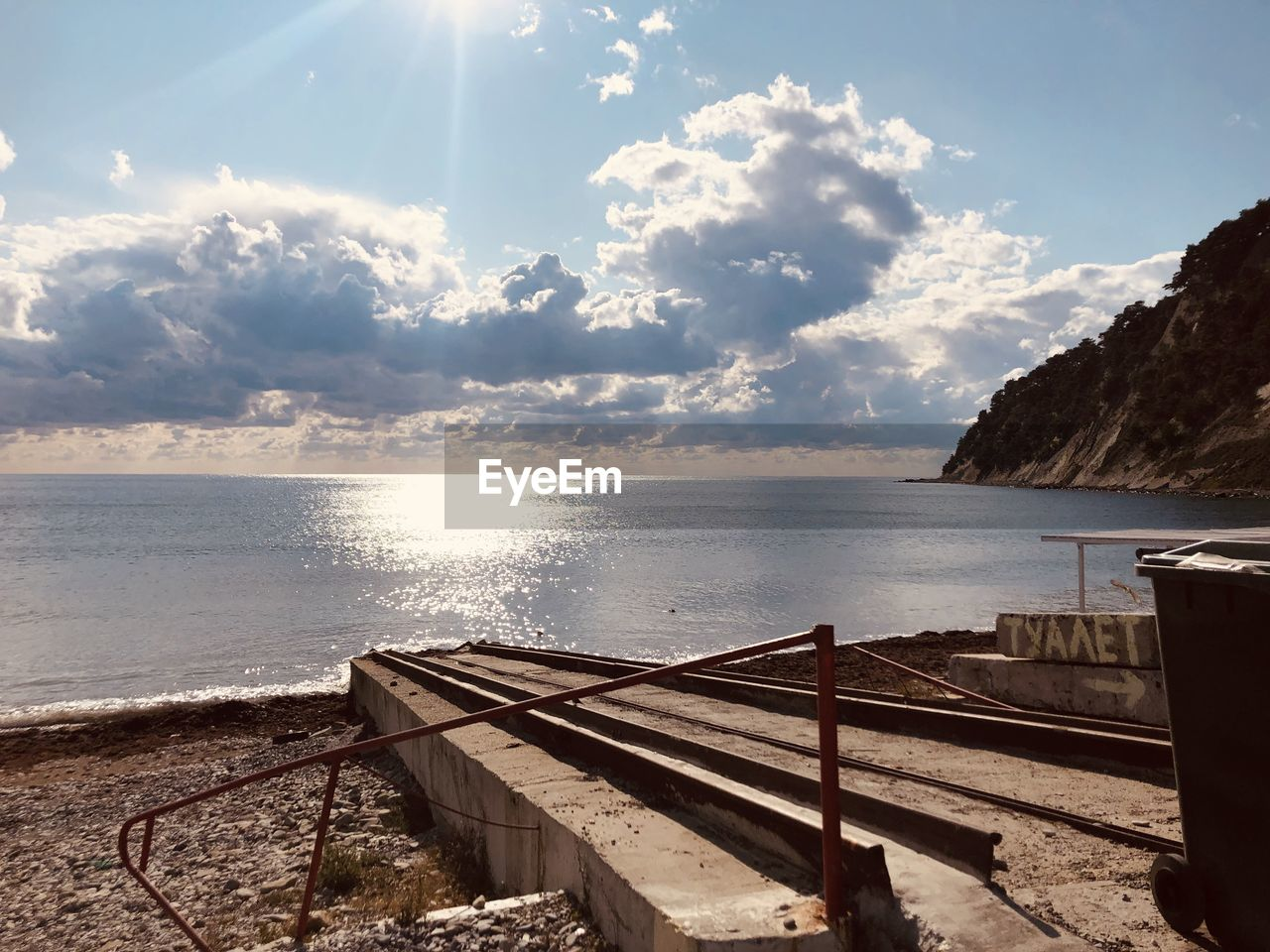 water, sky, sea, cloud - sky, beauty in nature, horizon, tranquility, tranquil scene, sunlight, horizon over water, scenics - nature, nature, land, railing, no people, beach, day, wood - material, non-urban scene, outdoors, sun, lens flare