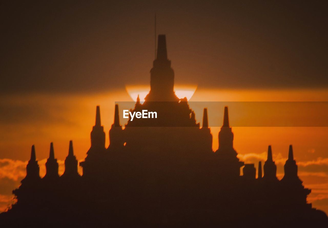 SILHOUETTE OF TEMPLE AGAINST BUILDING