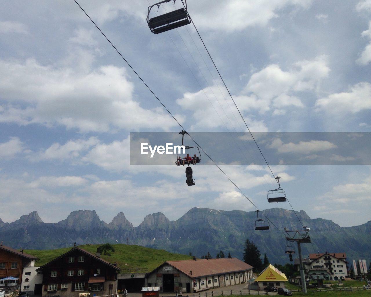 People sitting in ski lift against sky in flumserberg