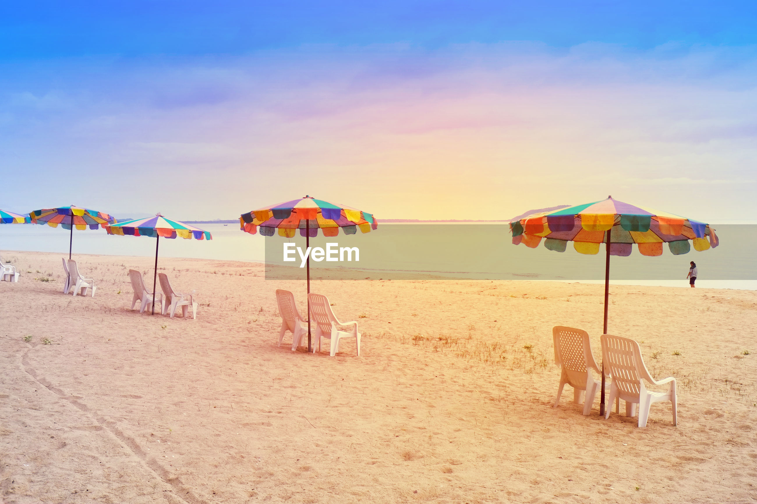 BEACH UMBRELLAS ON SHORE AGAINST SKY