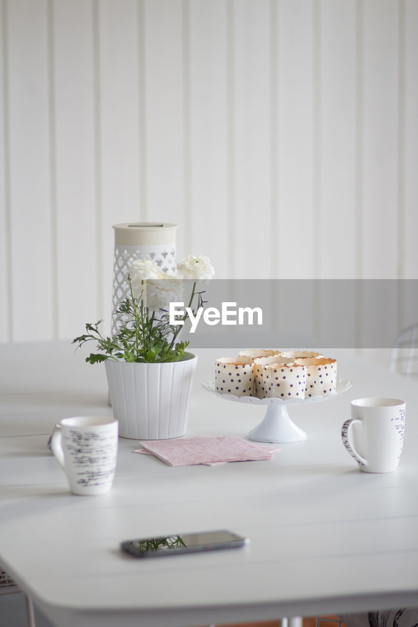 food and drink, table, food, cup, freshness, indoors, no people, drink, still life, plate, refreshment, mug, ready-to-eat, potted plant, kitchen utensil, saucer, tea, white color, breakfast, hot drink, crockery