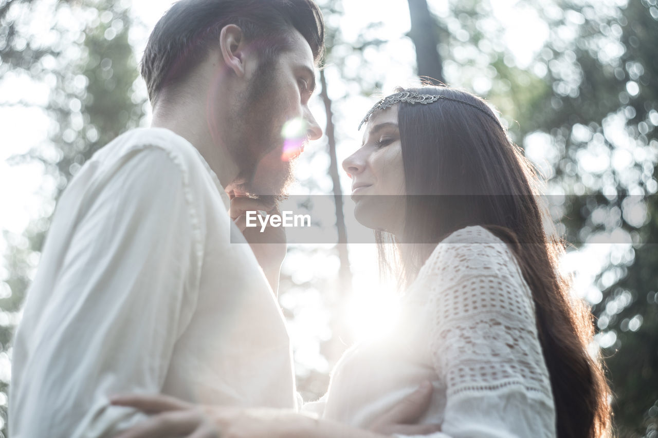 young adult, real people, women, young women, adult, togetherness, tree, lifestyles, emotion, side view, two people, love, leisure activity, positive emotion, day, people, nature, plant, sunlight, lens flare, outdoors, couple - relationship, hairstyle