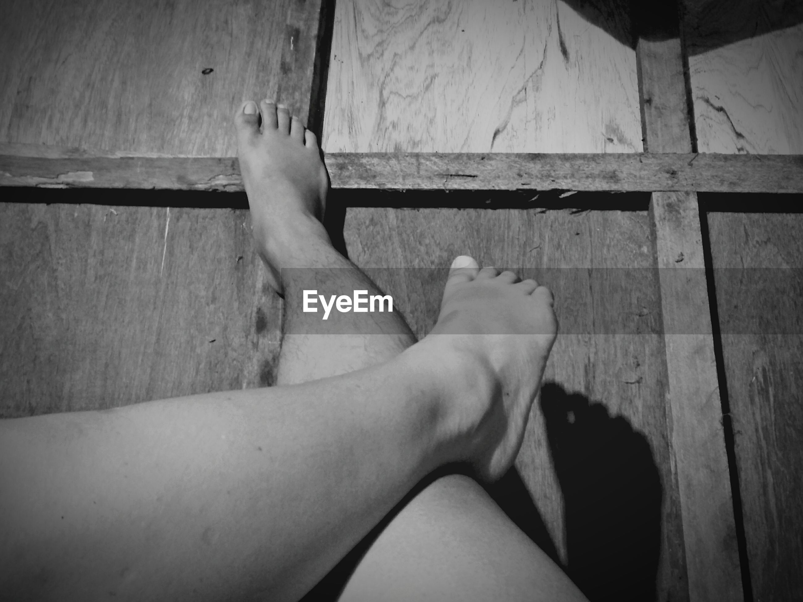 Low section of man and woman legs on wooden floor