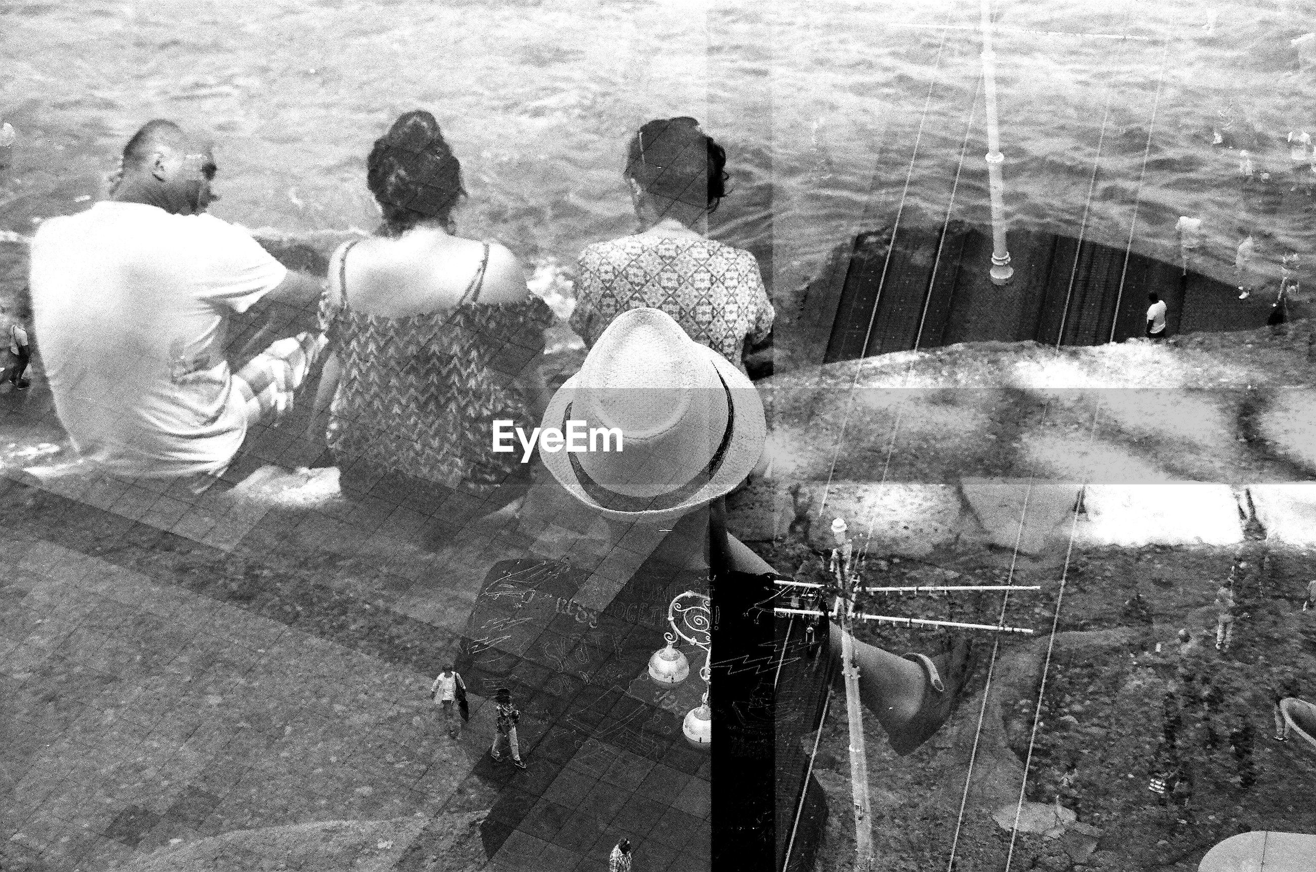 Double exposure of railroad tracks and people sitting by sea