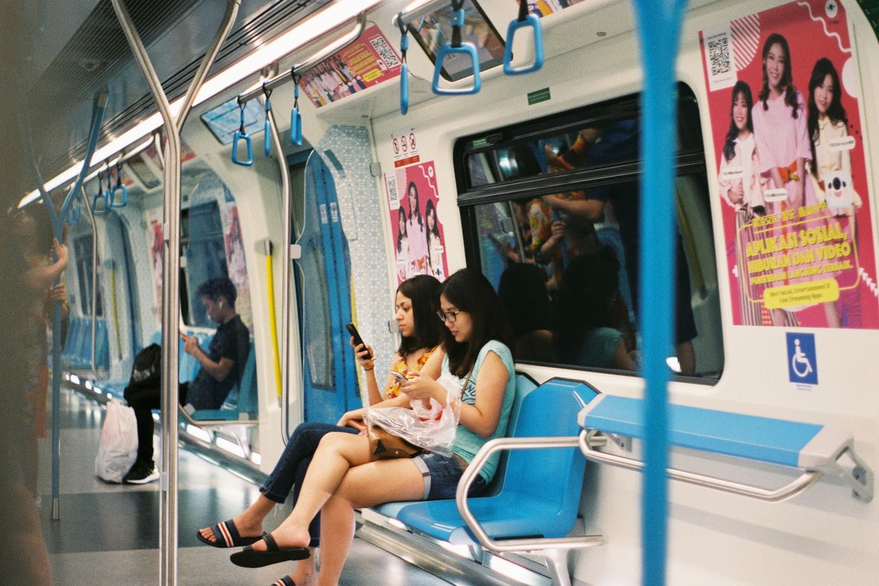 public transportation, sitting, mode of transportation, transportation, rail transportation, travel, train, seat, vehicle interior, vehicle seat, incidental people, train - vehicle, real people, group of people, women, passenger, people, subway train, journey, commuter, hairstyle, commuter train