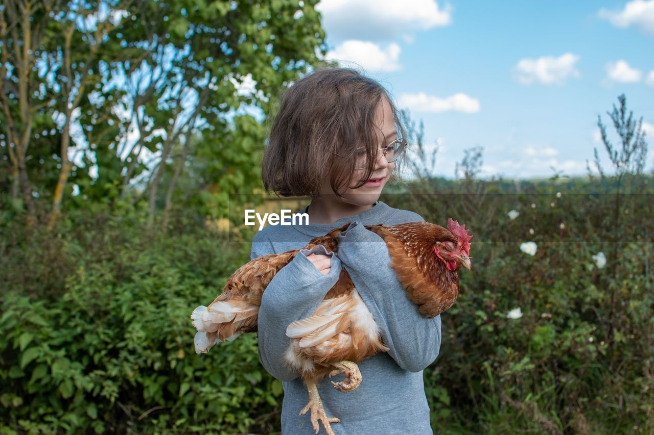 A child holding a hen