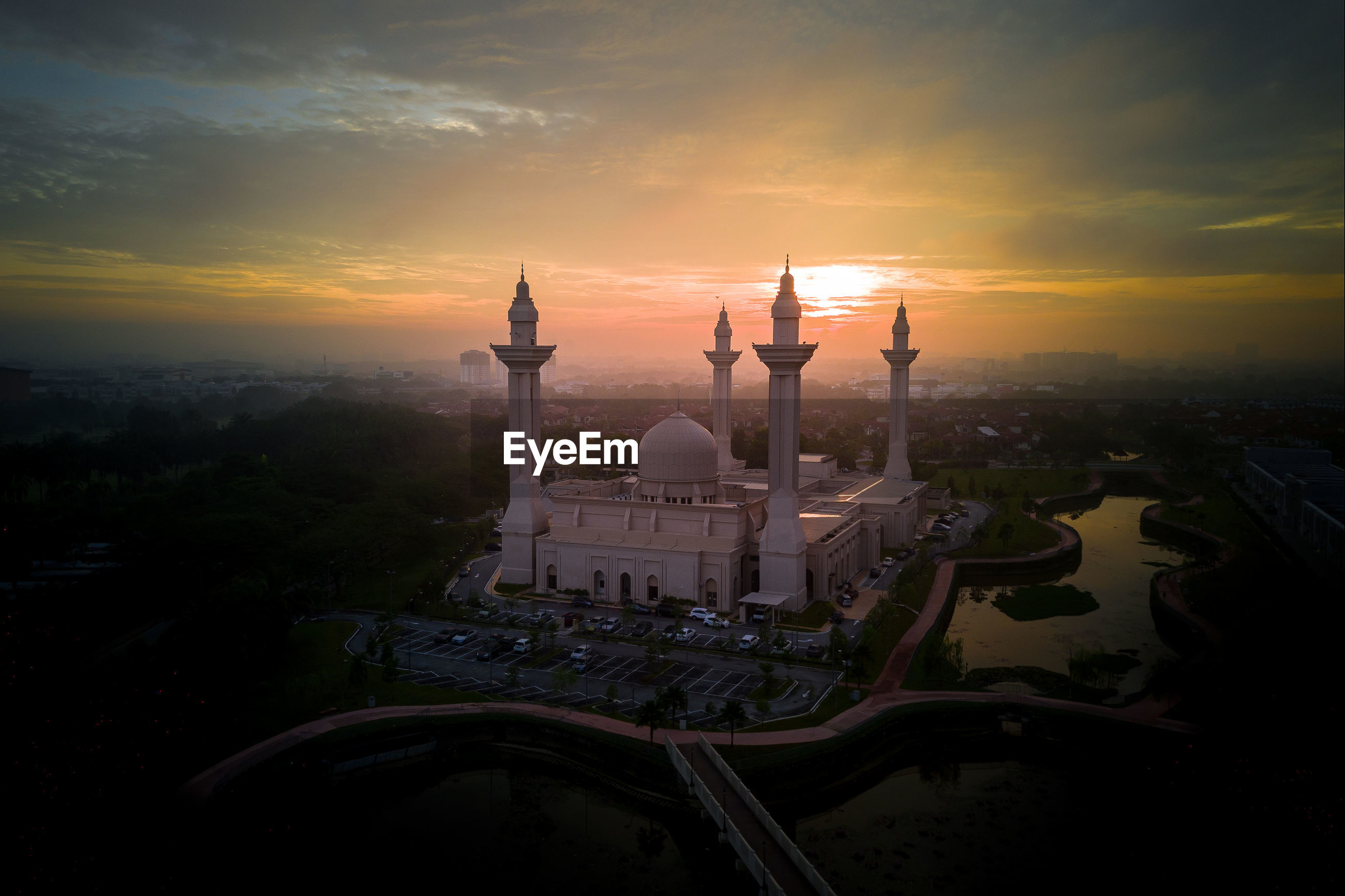 High angle view of mosque in city during sunrise