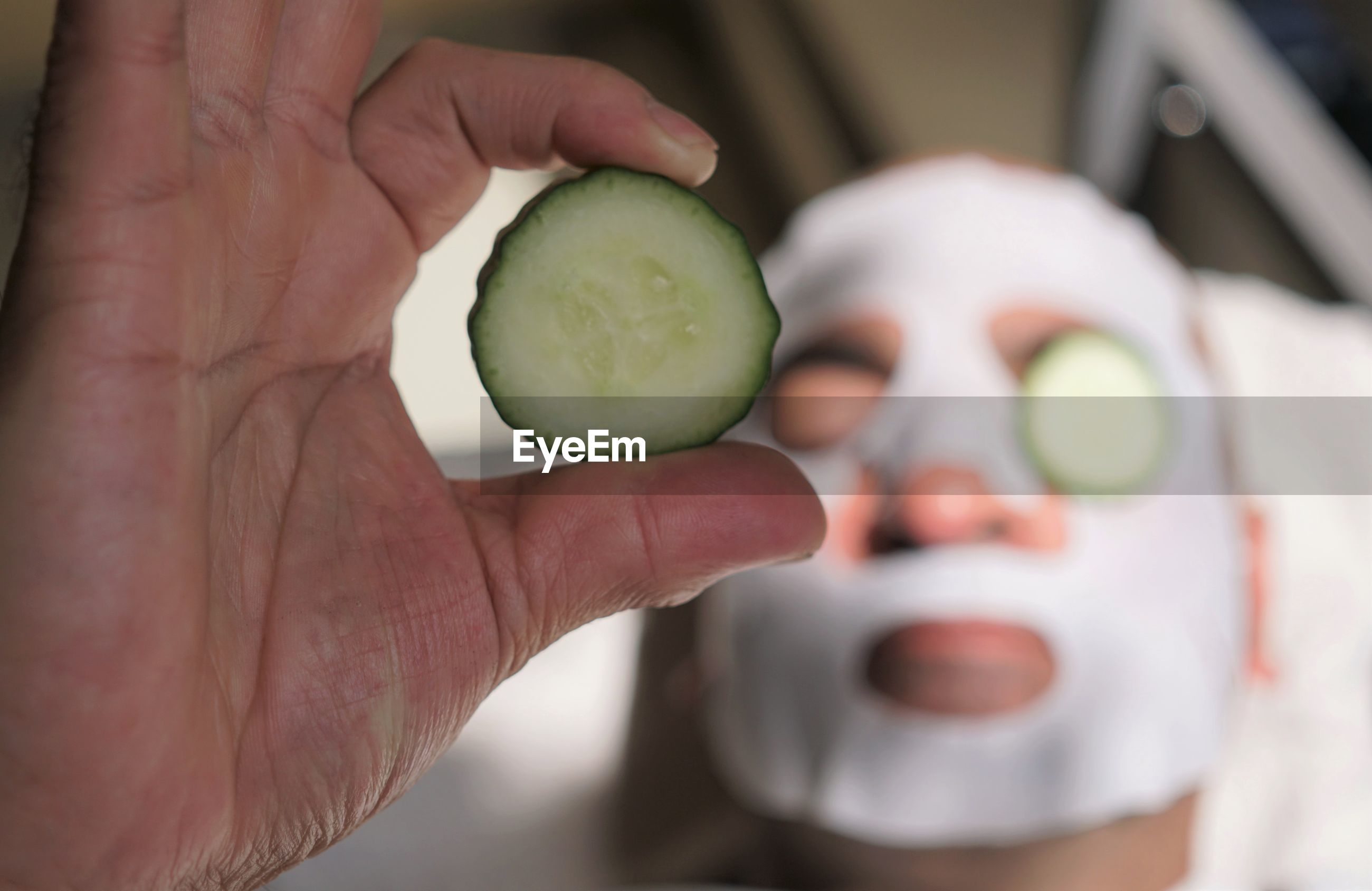 Close-up of man with facial mask on face holding cucumber