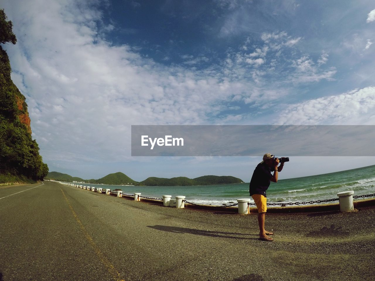 Man photographing through camera while standing at beach against sky