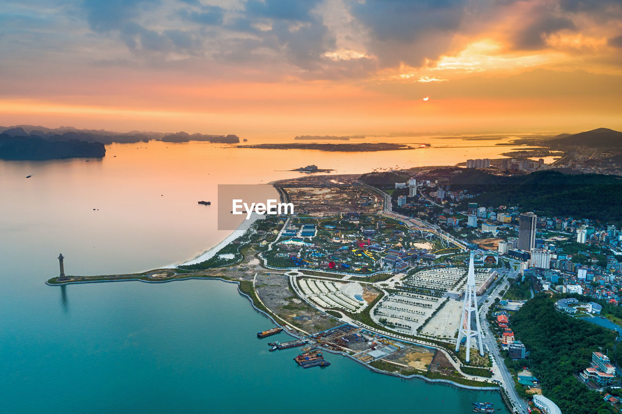 Aerial view of city by bay during sunset