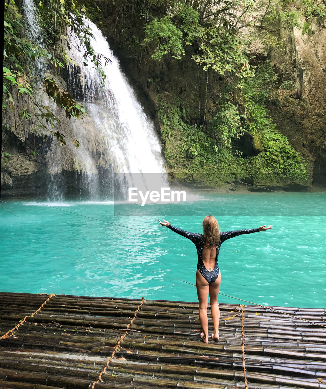 water, one person, beauty in nature, waterfall, real people, scenics - nature, human arm, leisure activity, arms outstretched, lifestyles, rear view, young adult, full length, young women, nature, motion, tree, vacations, limb, outdoors, flowing water