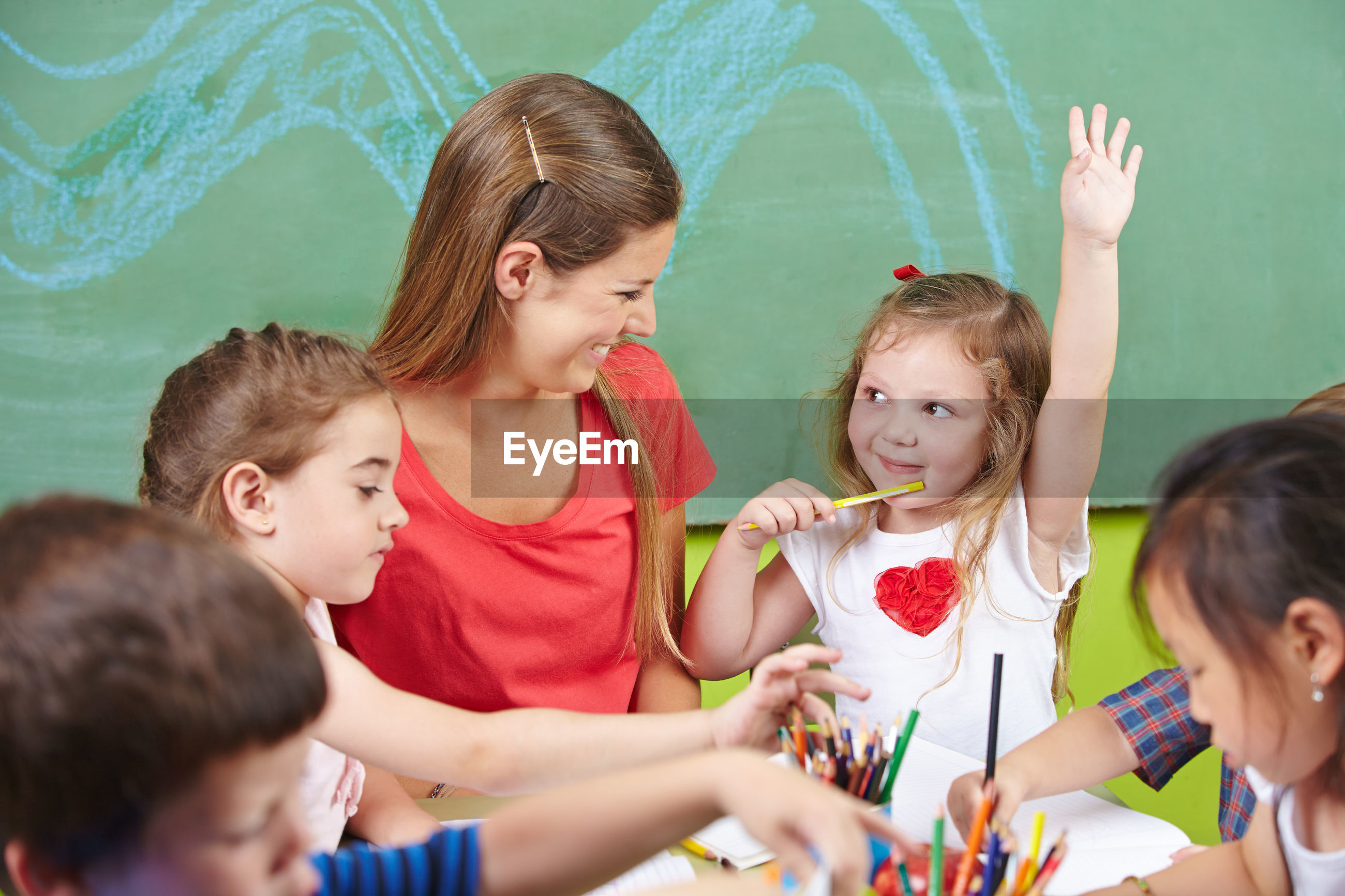 High angle view of smiling teacher with children in preschool