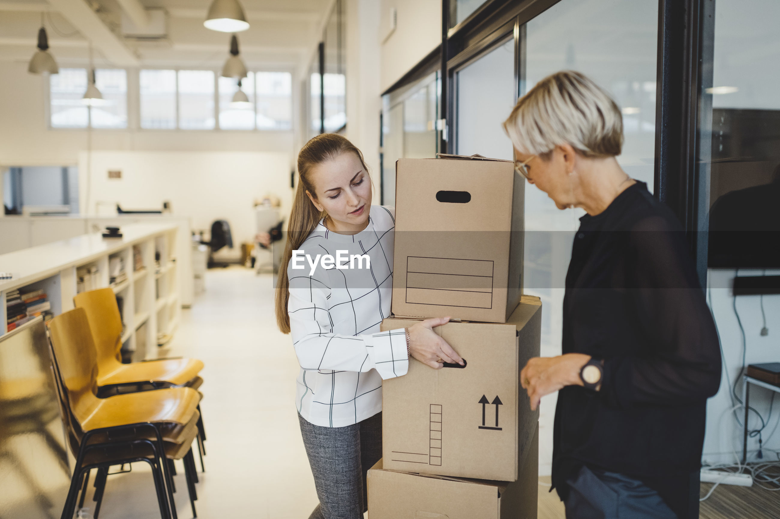 Mature businesswoman looking at female colleague carrying cardboard boxes in new office