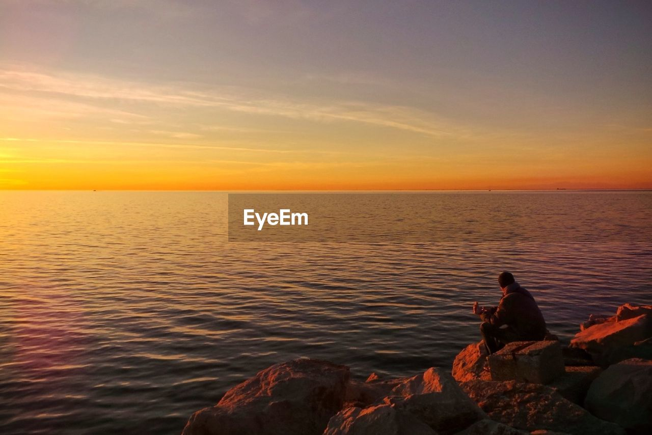 sunset, water, sea, nature, beauty in nature, scenics, real people, tranquil scene, tranquility, rock - object, sky, horizon over water, leisure activity, outdoors, vacations, sitting, women, men, lifestyles, adventure, full length, fishing pole, day, people