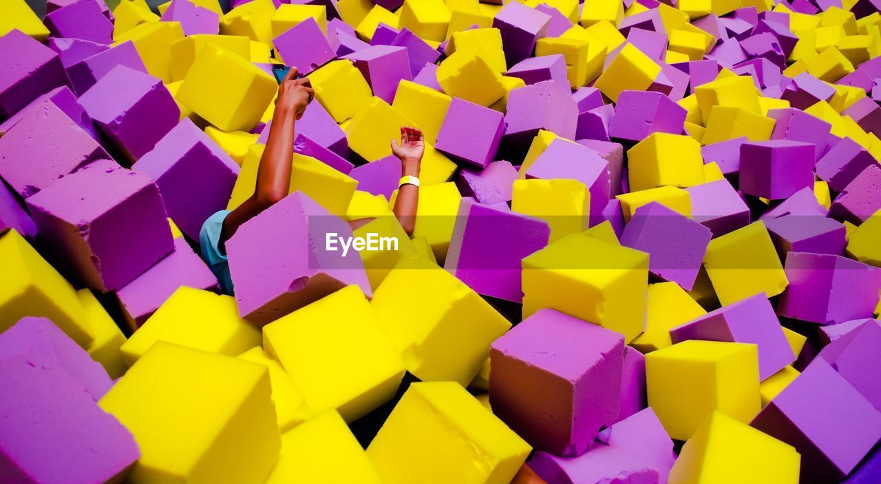 Cropped Image Of Man Amidst Stack Of Sponges