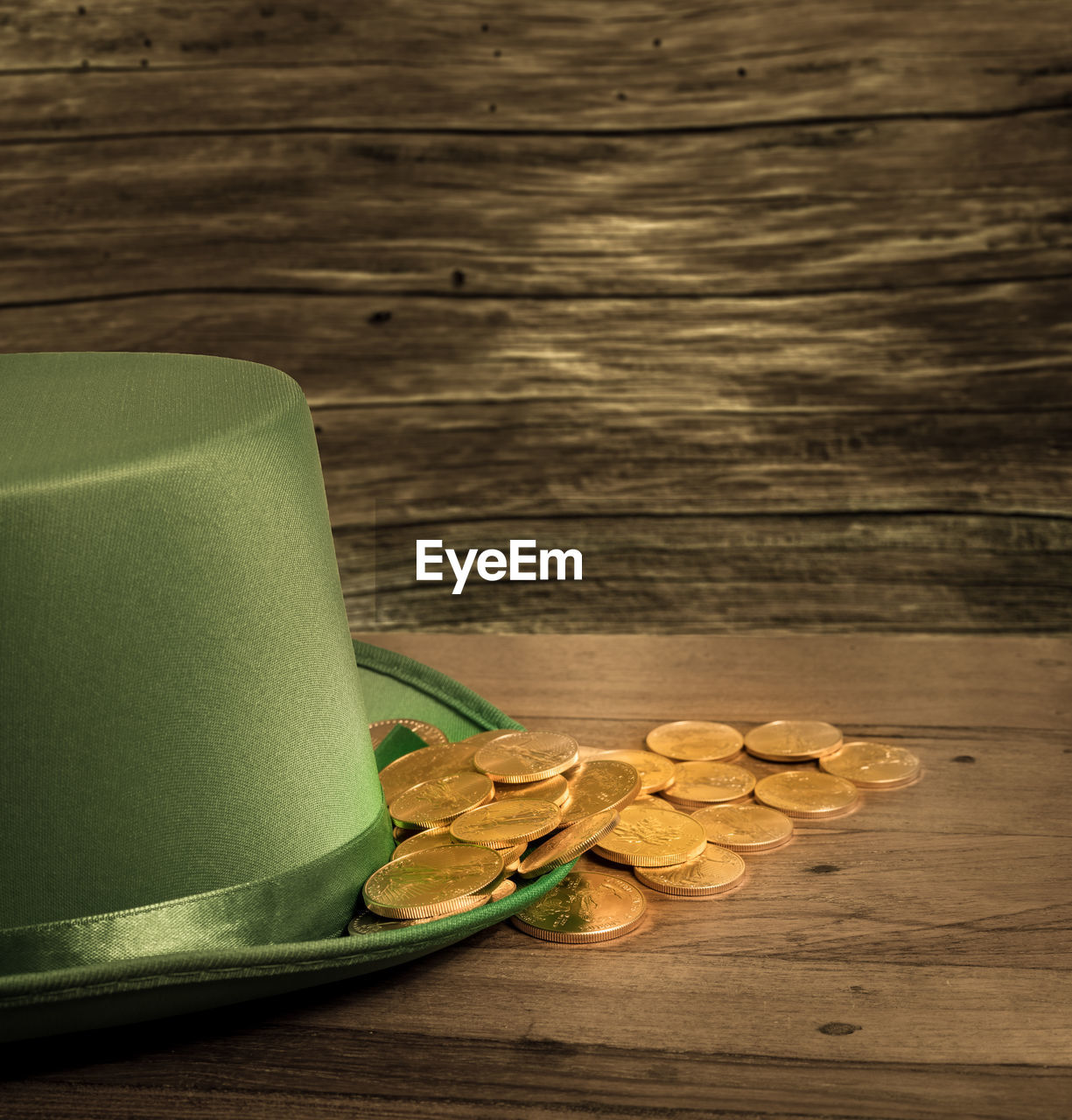Close-up of hat and coins on wooden table