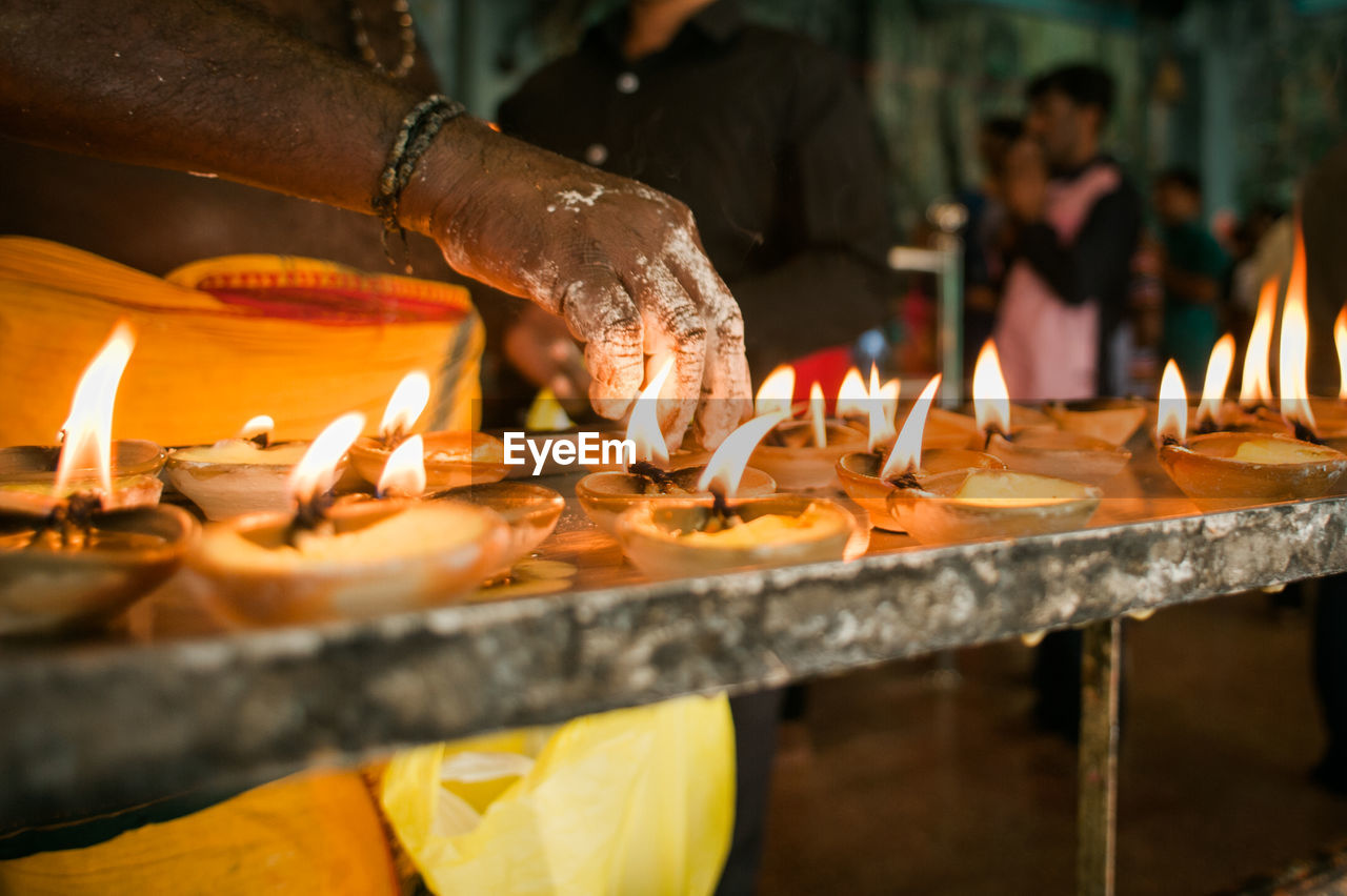 Cropped Hand Of Man Burning Candles In Temple