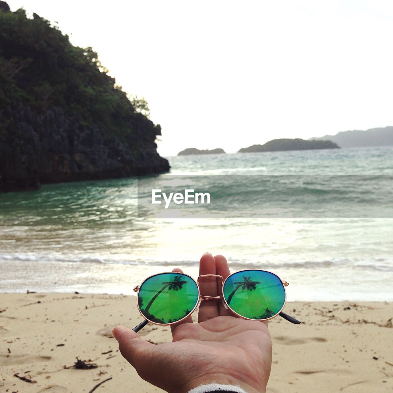Close-Up Of Hand Holding Sunglasses With Reflection At Beach