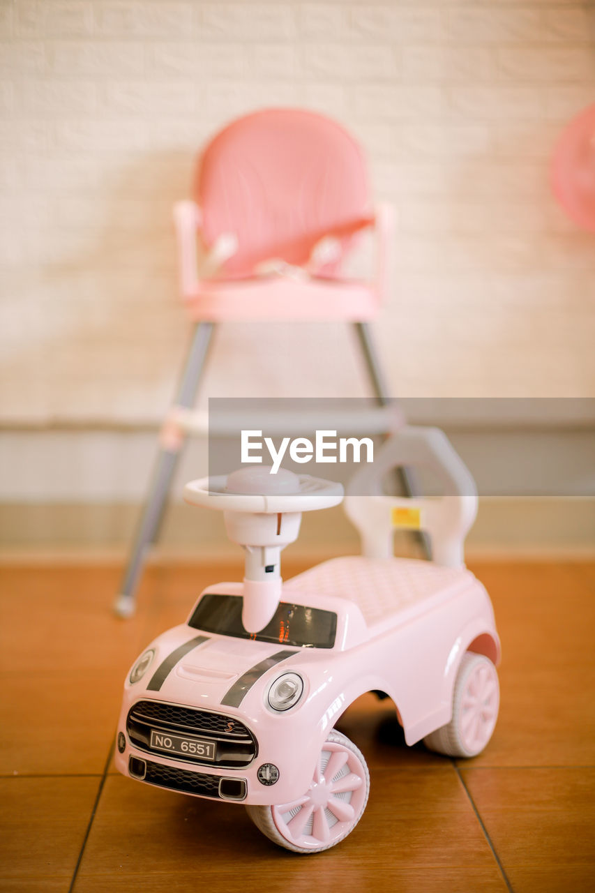 CLOSE-UP OF TOY CAR ON WOODEN TABLE