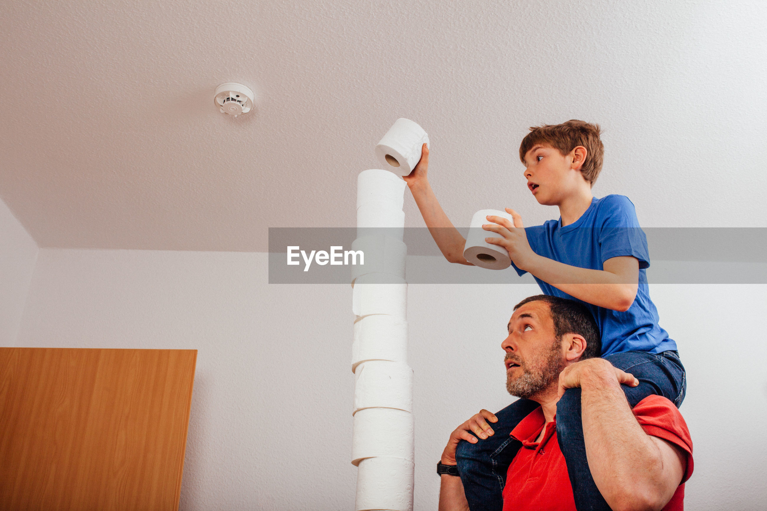 Man assisting boy stacking toilet papers