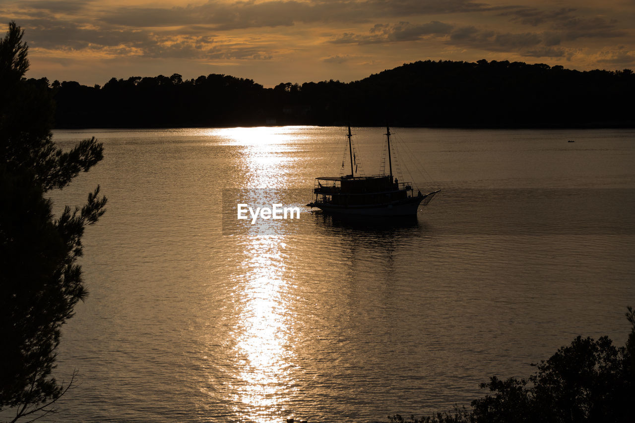 sunset, water, silhouette, sky, nature, nautical vessel, beauty in nature, cloud - sky, tree, scenics, reflection, waterfront, tranquility, transportation, tranquil scene, mode of transport, no people, outdoors, river, mountain, sailing, day