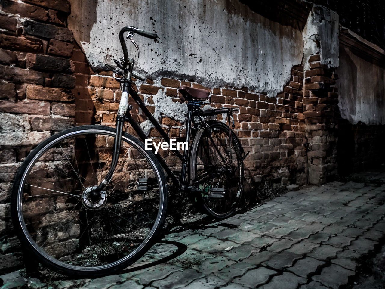 Bicycle parked against weathered brick wall in alley
