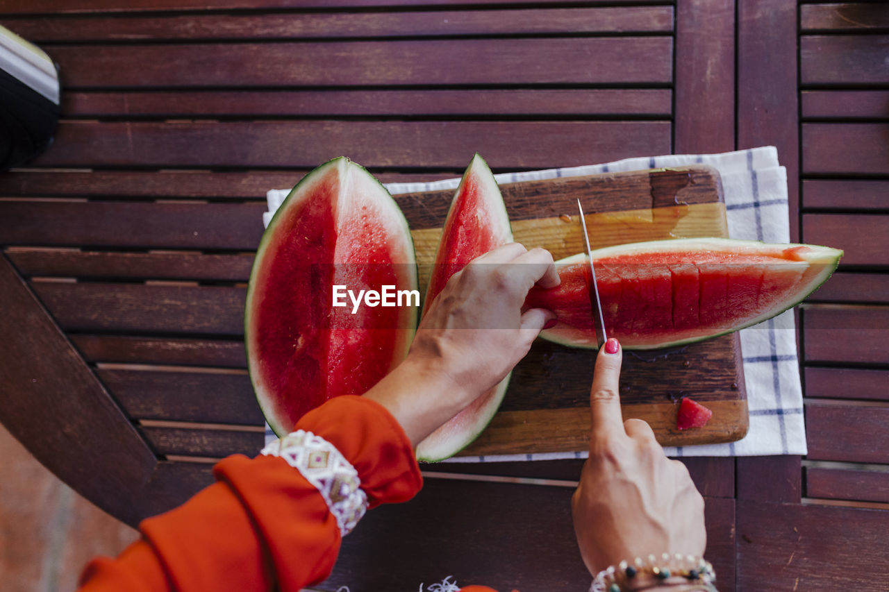 food and drink, food, fruit, healthy eating, freshness, watermelon, wellbeing, table, real people, slice, red, wood - material, one person, holding, human hand, lifestyles, hand, human body part, day