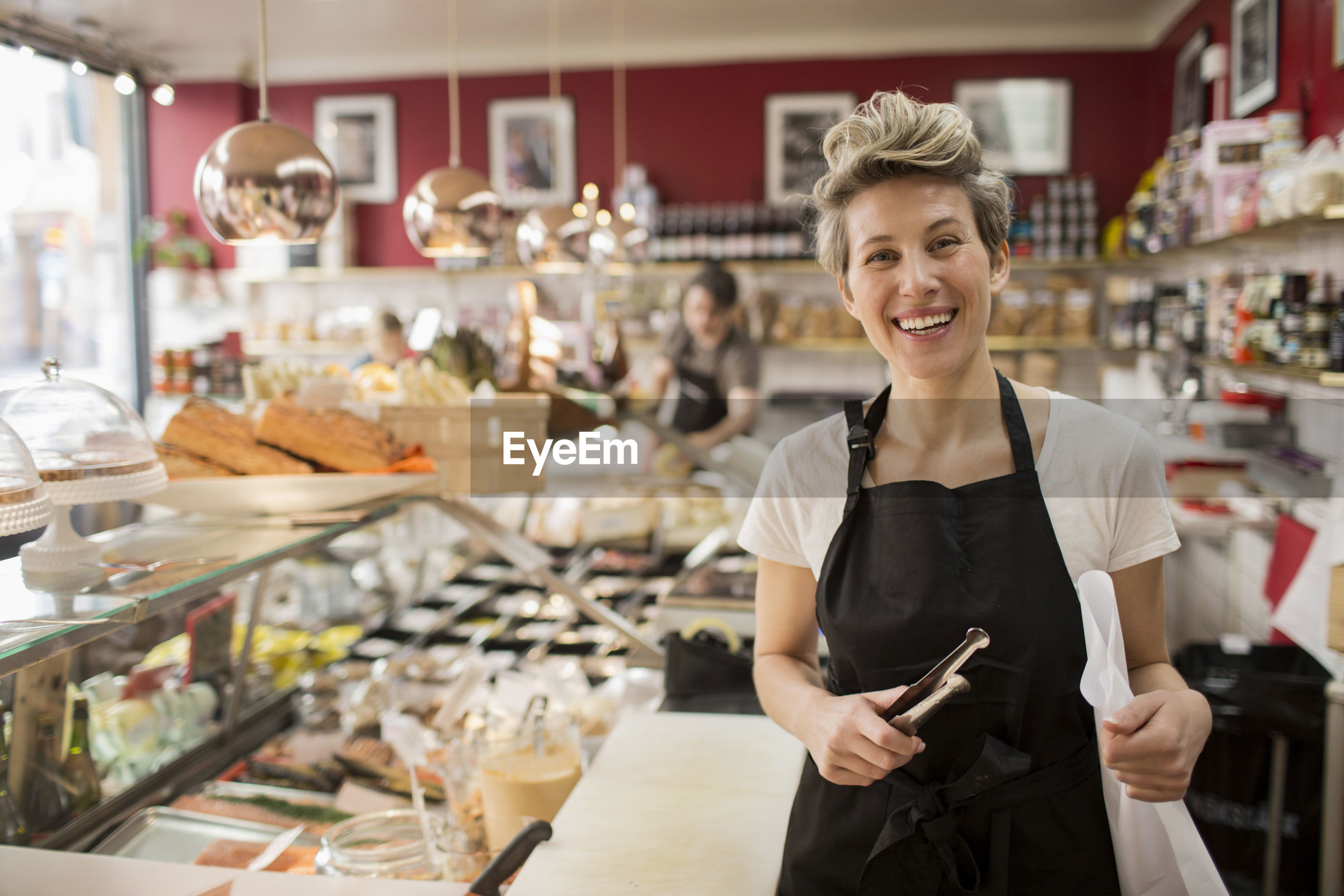 PORTRAIT OF A SMILING YOUNG WOMAN STANDING AT STORE