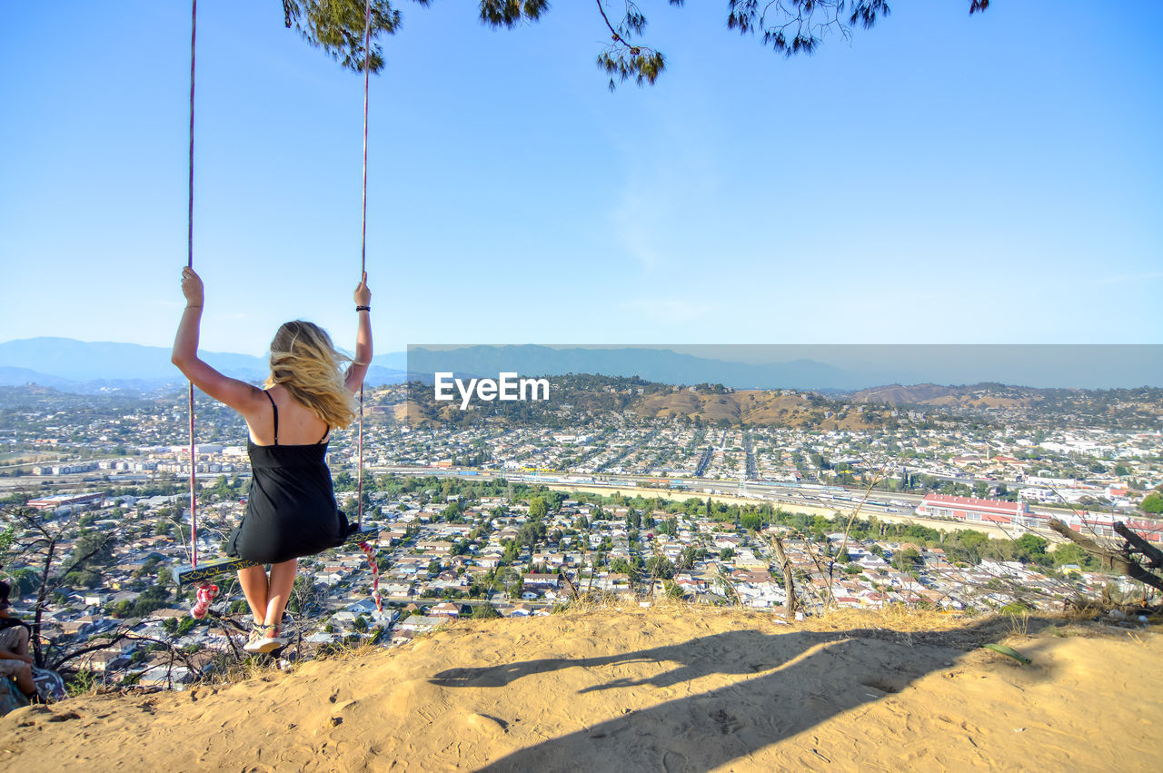 Rear view of woman on swing against cityscape