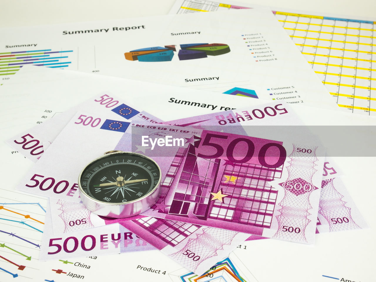 Close-Up Of Five Hundred Euro Banknotes With Graphs On Table