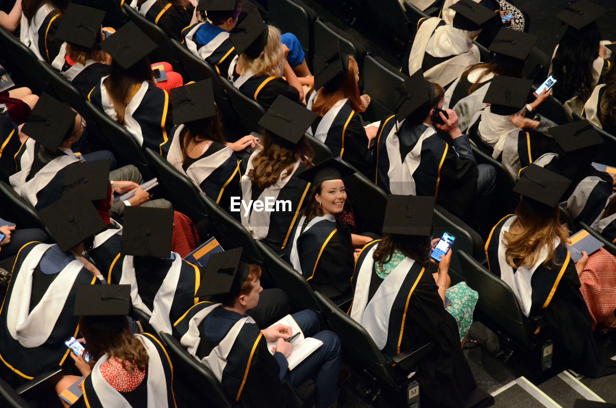 High angle view of students in graduation gown sitting on chairs