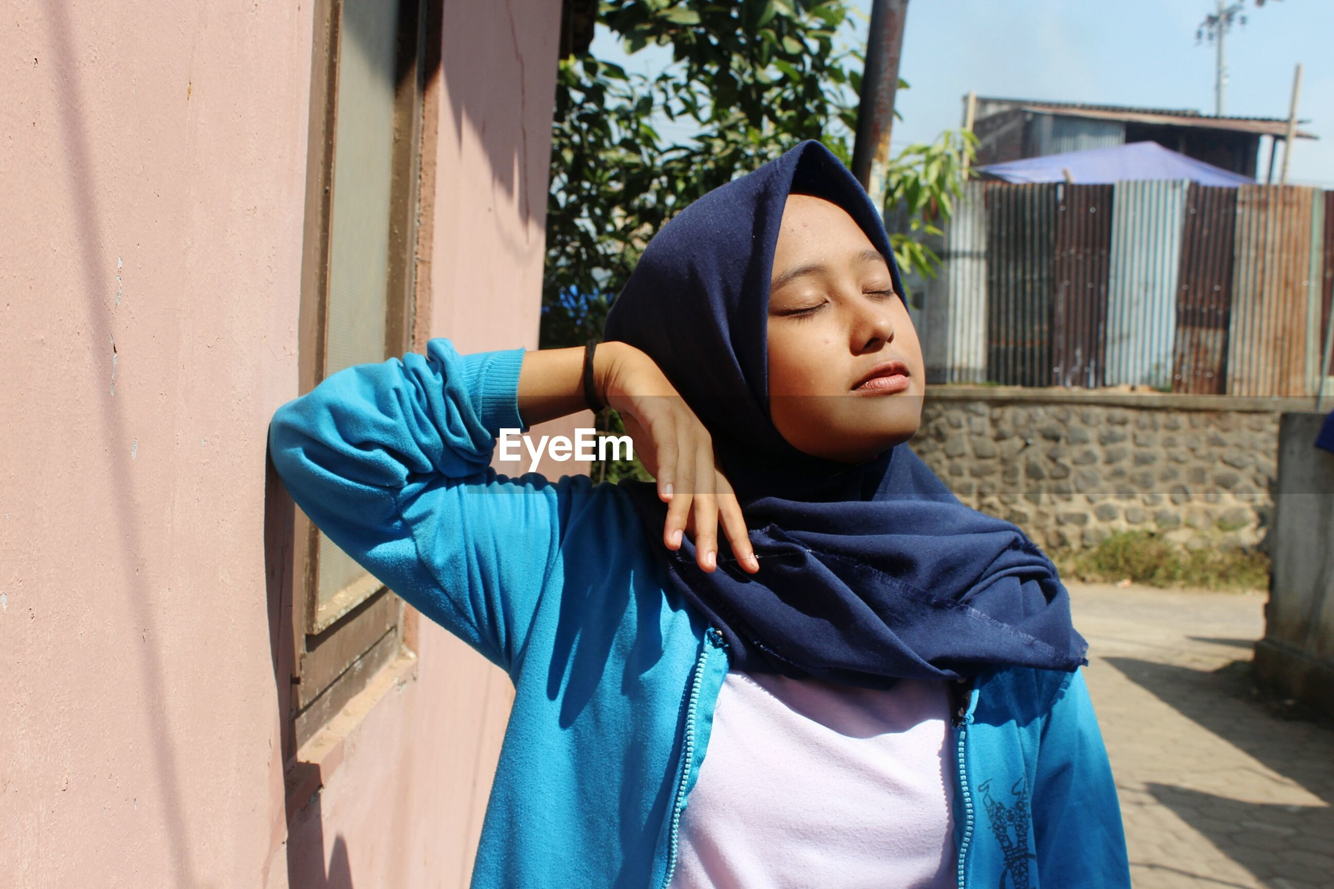 Young woman with eyes closed wearing hijab by house