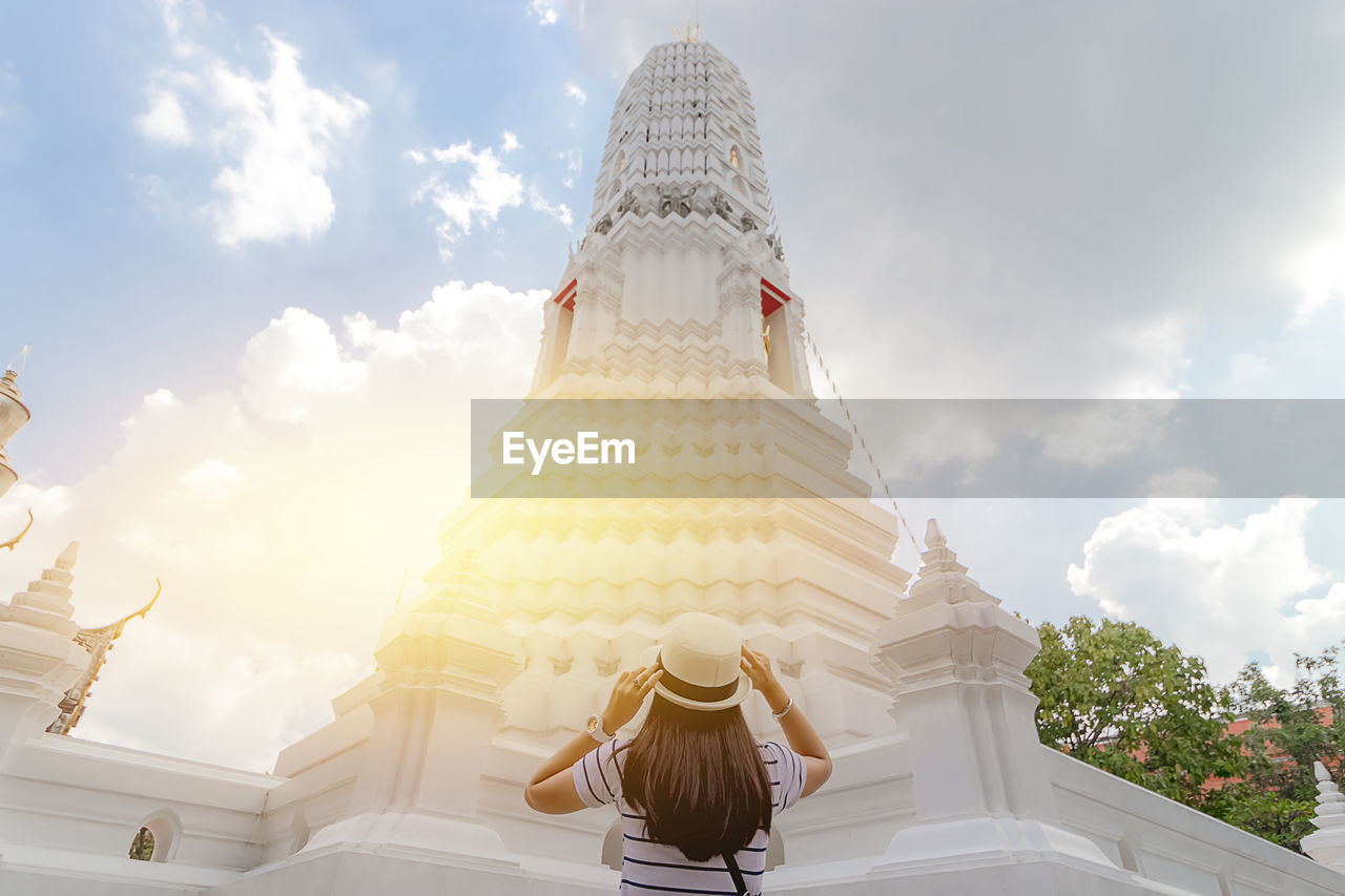 Rear view of woman standing towards pagoda against cloudy sky