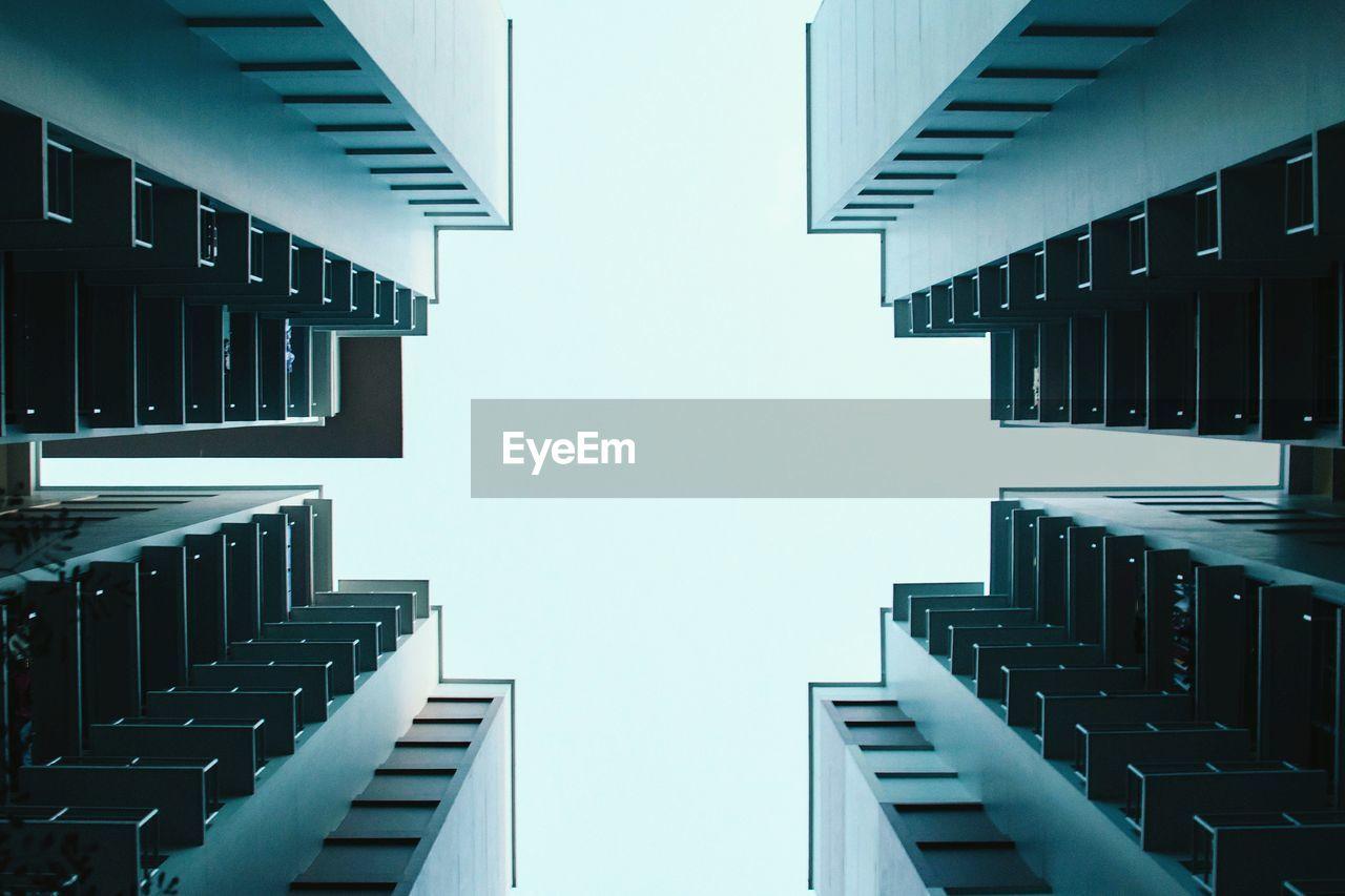 Directly below shot modern buildings against clear sky