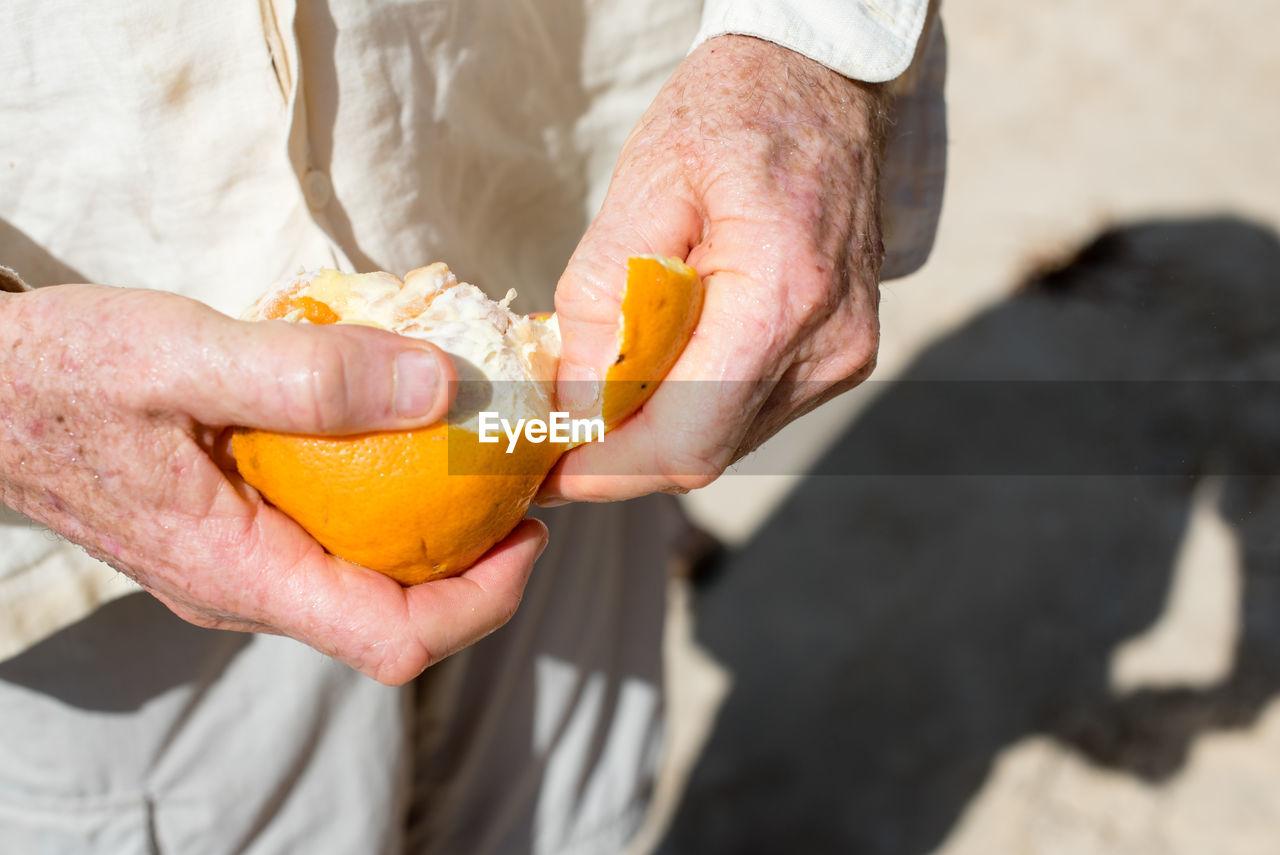 Close-Up Of Man Peeling Orange Outdoors