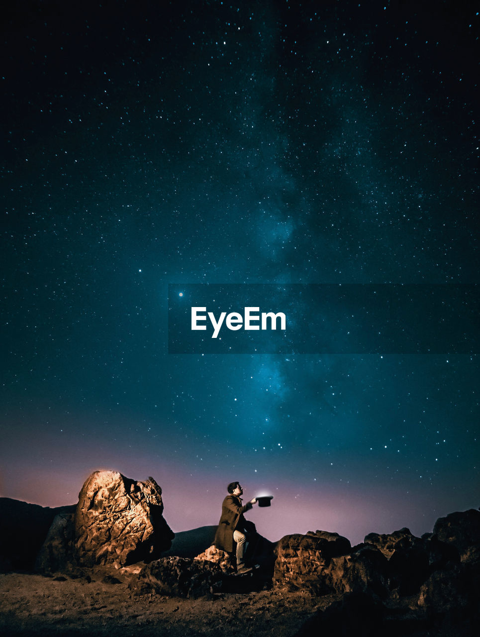 MAN SITTING ON ROCK AGAINST STAR FIELD AT NIGHT