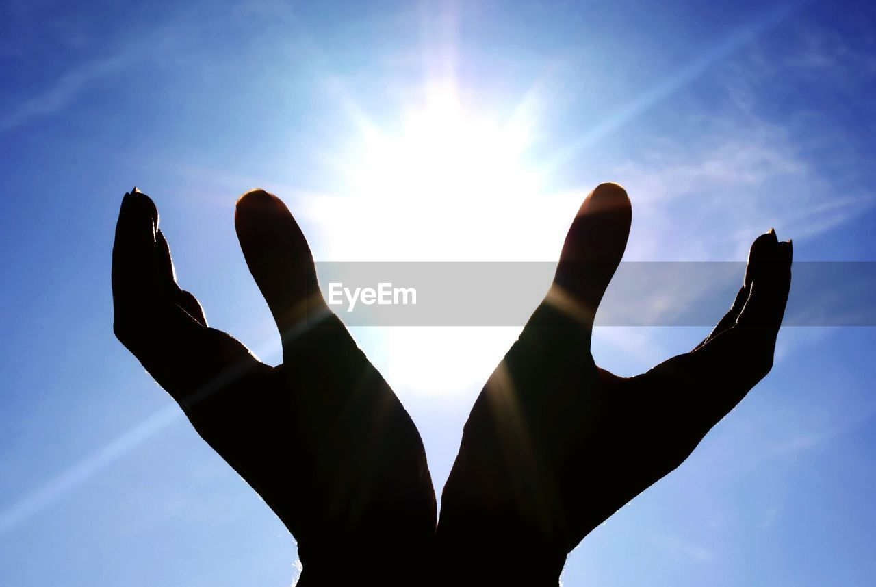 Optical Illusion Of Silhouette Hands Holding Sun Against Sky