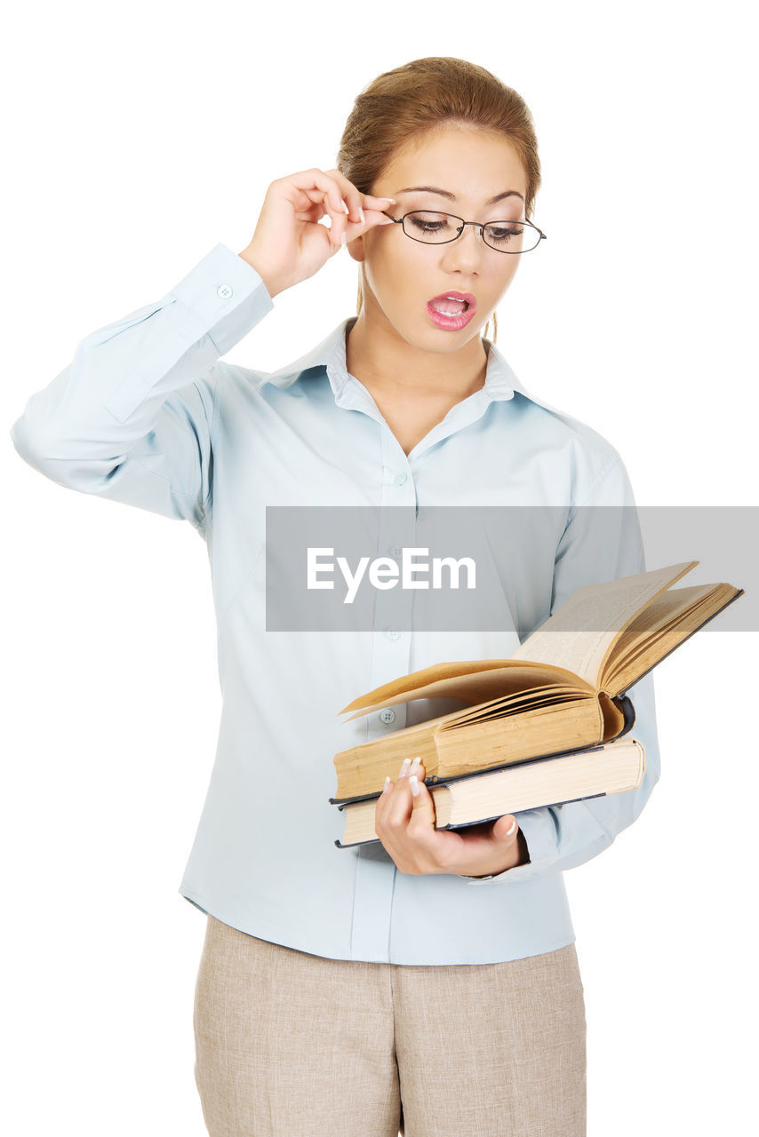 Young businesswoman holding book standing against white background