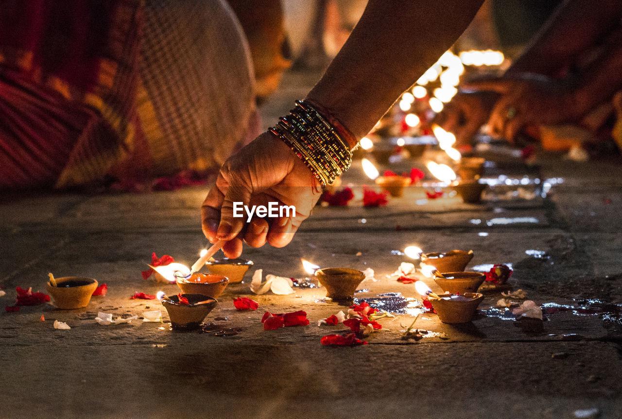 Close-Up Of Hand Holding Illuminated Candles