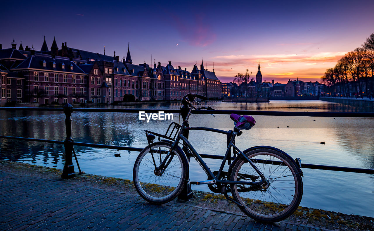 Bicycle parked on footbridge over river against sky during sunset