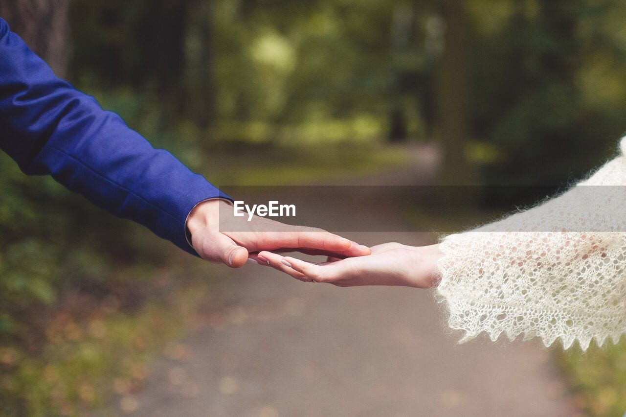 Cropped image of couple holding hands at park