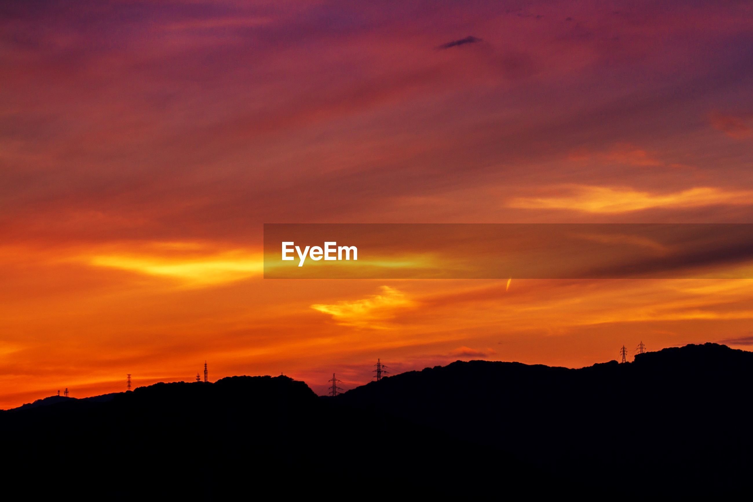Silhouettes of electricity pylons at scenic sunset