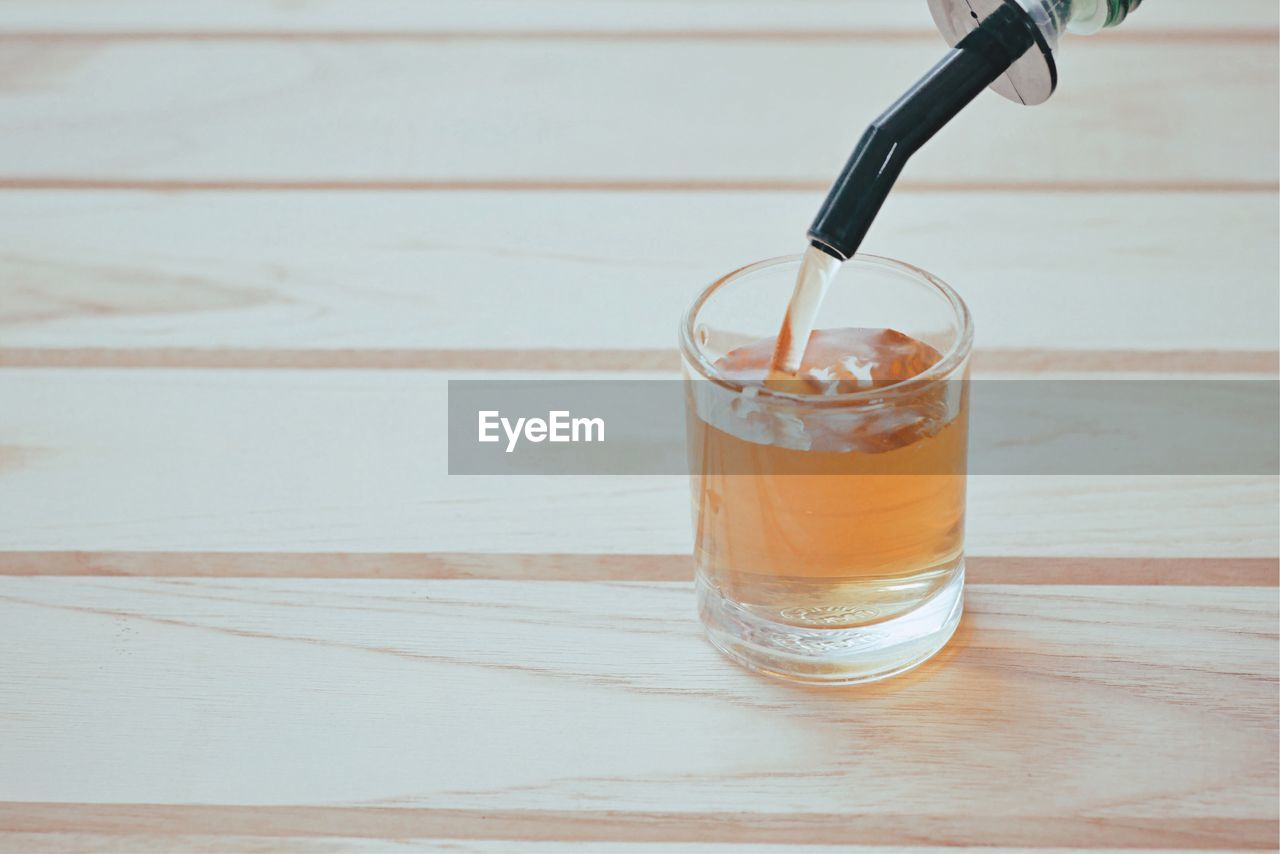 drink, refreshment, table, glass, food and drink, wood - material, drinking glass, household equipment, freshness, still life, drinking straw, indoors, straw, close-up, no people, glass - material, food, focus on foreground, high angle view, non-alcoholic beverage, wood grain