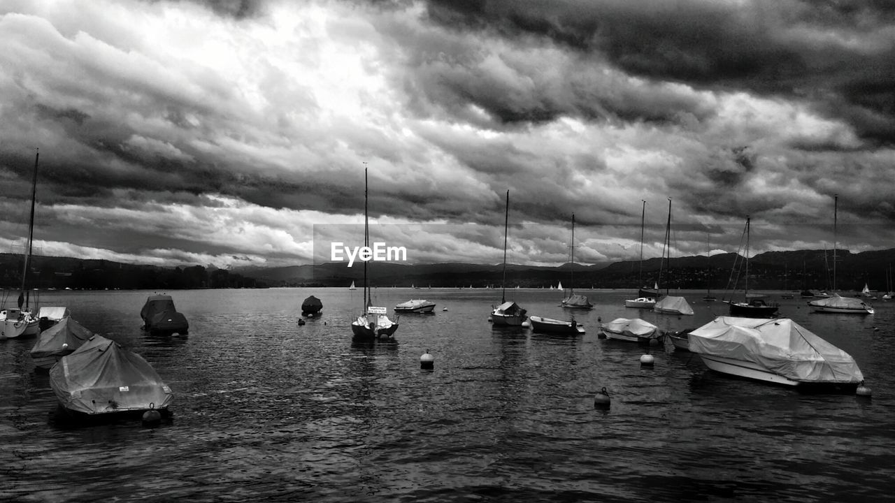 Sailboats on lake zurich against cloudy sky