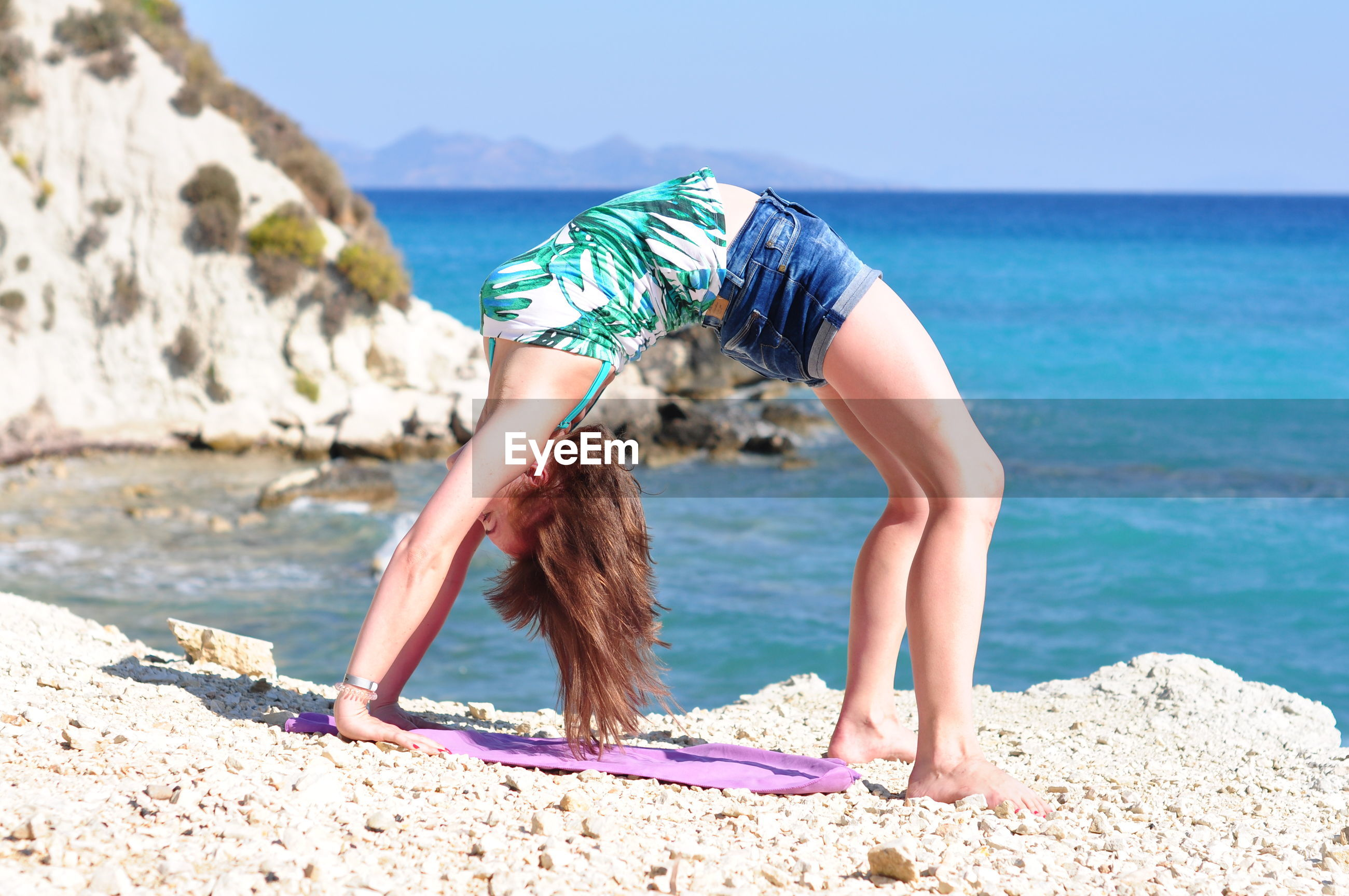 Full length of woman practicing yoga on rocks at beach